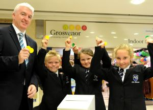 Ed Kennedy, manager of the Grosvenor Centre in Macclesfield, with pupils from Ash Grove Academy primary school, winners of last year's  Shop for Schools contest,